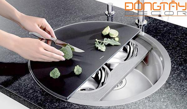 Bồn rửa đă năng với lớp trên cùng là thớt bằng kính, ở giữa là hai chiếc bát rửa mini có thể tháo lắp dễ dàng. Dưới cùng là bồn rửa lớn và hệ thống thoát nước.