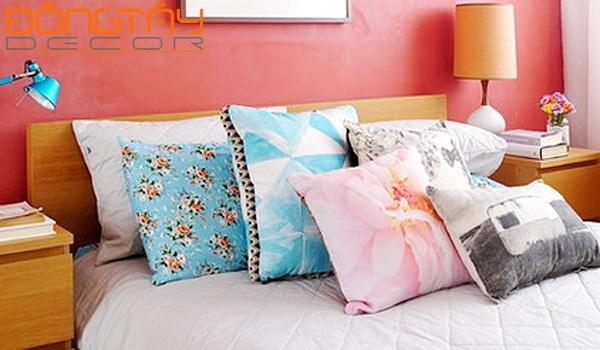 Những chiếc gối nhiều màu nổi bật trên gam màu trung tính của chăn, ga giường